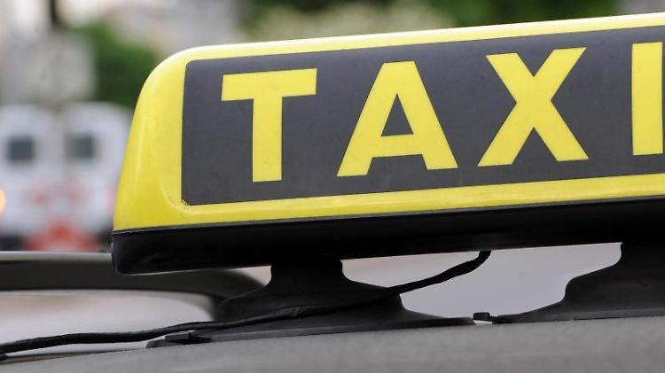 Ein Taxischild spiegelt sich in einem Autodach. Foto: Franziska Kraufmann/Archivbild