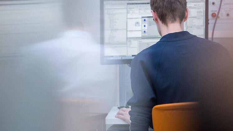 Ein Auszubildender der Mechatronik programmiert an einem Computer. Foto: Sebastian Gollnow/Archivbild