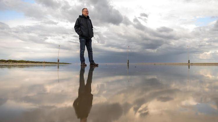 Stephan Weil (SPD), Ministerpräsident von Niedersachsen, steht auf der Nordseeinsel Norderney am Strand. Foto: Mohssen Assanimoghaddam