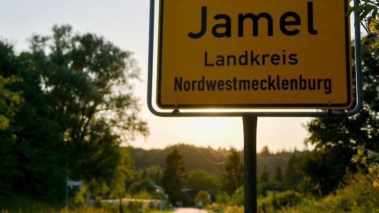 Die Sonne steht hinter dem Ortsschild von Jamel. Foto: Axel Heimken/Archivbild