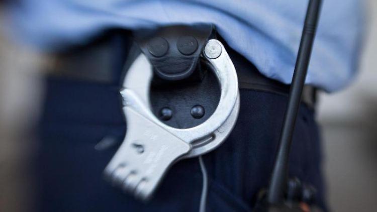 Handschellen sind an dem Gürtel einesJustizbeamten angebracht. Foto: Friso Gentsch/Archivbild