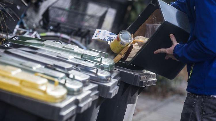 Ein junger Mann schüttet Abfall in eine Mülltonne. Foto: Frank Rumpenhorst/Archivbild