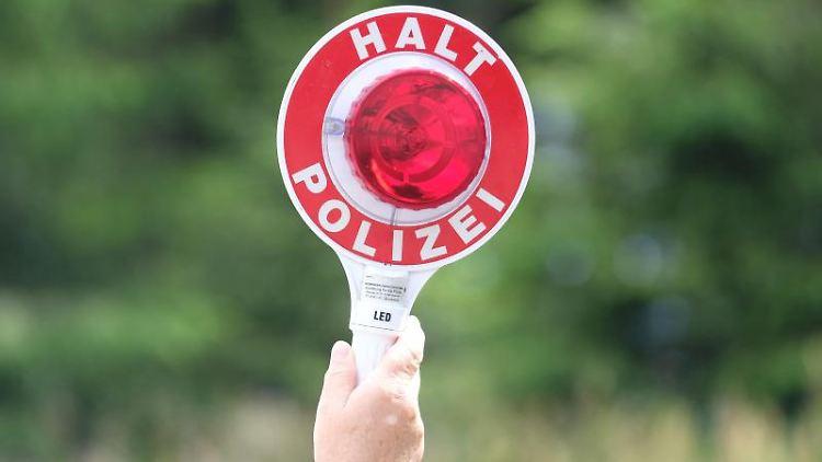 Eine Polizistin hält während einer Polizeikontrolle eine rote Winkerkelle in die Höhe (Symbolbild). Foto: Sebastian Willnow/Archivbild