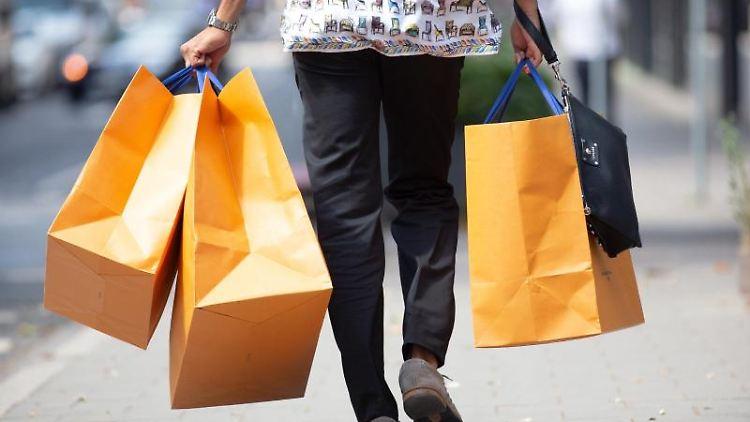 Ein Mann geht mit Einkaufstüten über eine Straße. Foto: Martin Gerten