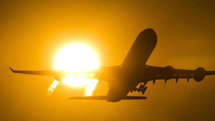 Ein Flugzeug startet in den Sonnenuntergang. Foto: Daniel Reinhardt/Archiv