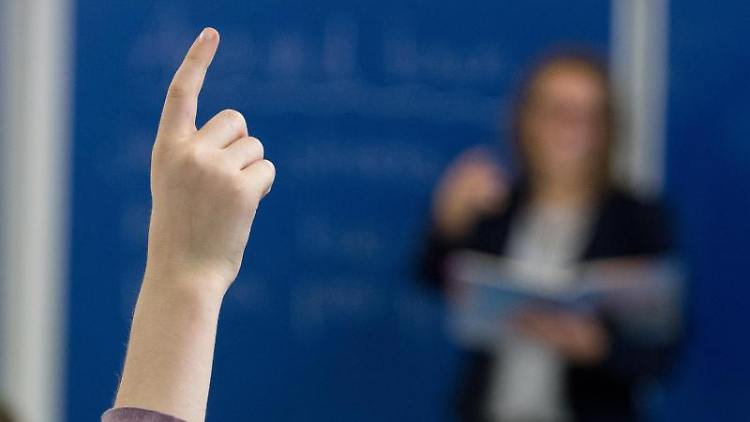 Ein Schüler an einem Gymnasium meldet sich im Unterricht. Foto: Armin Weigel/Archiv