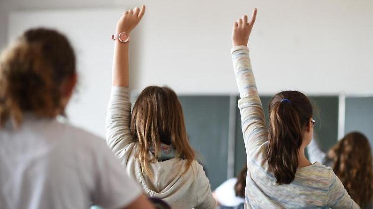 Zwei Schülerinnen melden sich im Unterricht. Foto: Felix Kästle/Archiv
