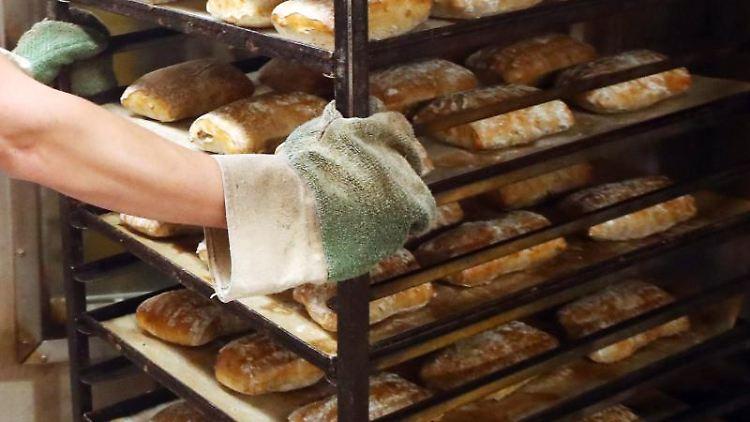 Ein Bäcker holt frisch gebackene Brote aus einem Backofen. Foto: Bodo Schackow/Archivbild