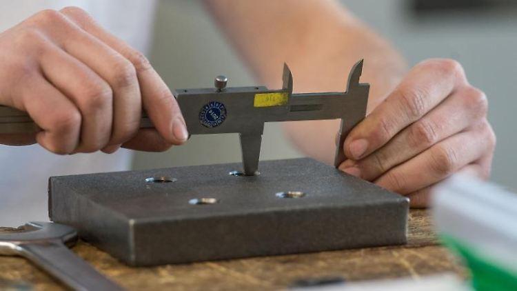 Ein Auszubildender misst ein Werkstück mit einer Schieblehre aus. Foto: Patrick Seeger/Archivbild
