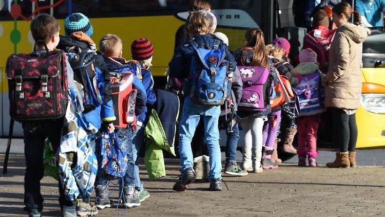 Mehrere Schüler steigen in einen Schulbus ein. Foto: Felix Kästle/Archiv