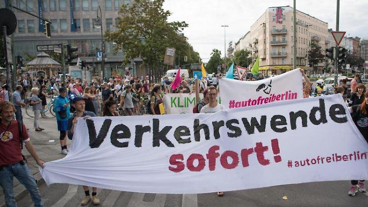 Menschen demonstrieren und halten dabei ein Transparent mit der Aufschrift