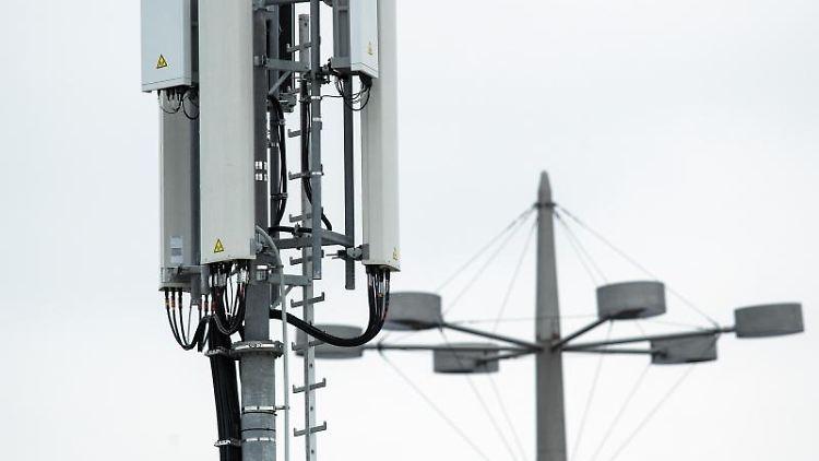 Mobilfunkantennen für das 5G-Netz sind an der Spitze eines Mobilfunkmastes angebracht. Foto: Federico Gambarini/Archivbild
