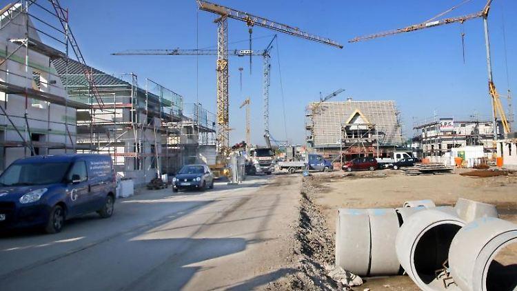 Kräne versorgen Bauarbeiter in einem Neubaugebiet mit Baumaterial. Foto: Roland Weihrauch/Archivbild