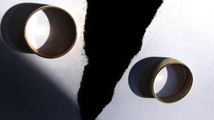 Zwei getragene Eheringe auf einem zerrissenen Papier. Foto: Karl-Josef Hildenbrand/Archivbild