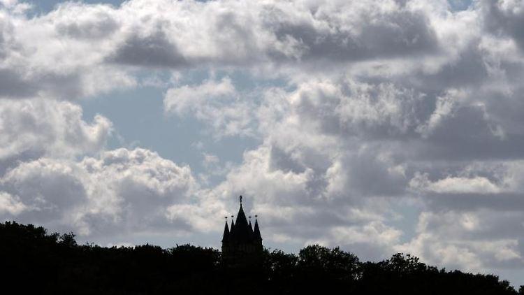 Dunkle Wolken ziehen über den Babelsberg mit dem Flatowturm in Potsdam. Foto: Ralf Hirschberger/Archivbild