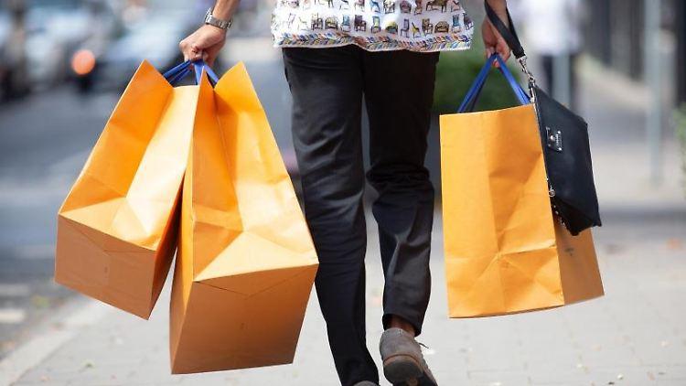 Ein Mann mit Einkaufstüten. Foto: Martin Gerten/Archivbild