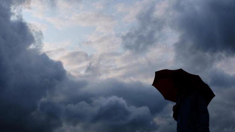 Ein Mann geht mit einem Regenschirm vor aufziehenden dunklen Wolken spazieren. Foto: Martin Gerten/Archivbild