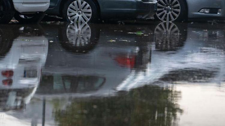 Autos parken inmitten einer großen Pfütze, die sich nach einem starken Gewitter gebildet hatte. Foto:Frank Rumpenhorst