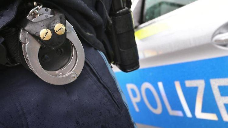 Ein Polizist steht mit Handschellen und einer Pistole am Gürtel vor einem Streifenwagen.Foto: Karl-Josef Hildenbrand/Archivbild