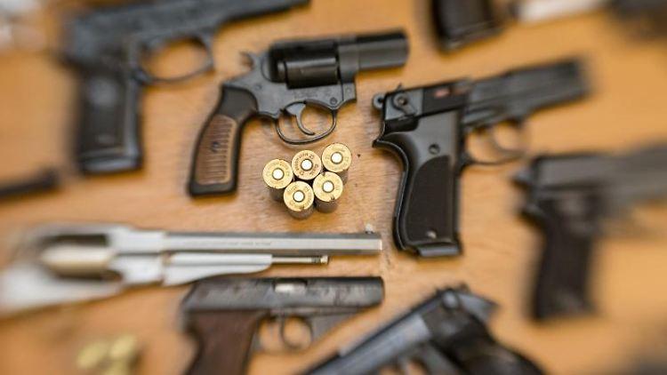 Pistolen, Revolver und Munition liegen nebeneinander aufgereiht. Foto: Friso Gentsch/Archiv