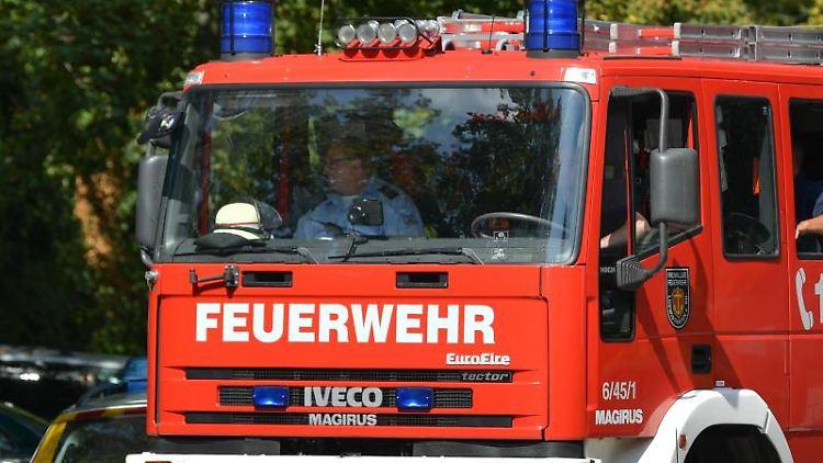 Ein Feuerwehrfahrzeug fährt an einer Straßensperre vorbei. Foto: Uwe Anspach/Archivbild