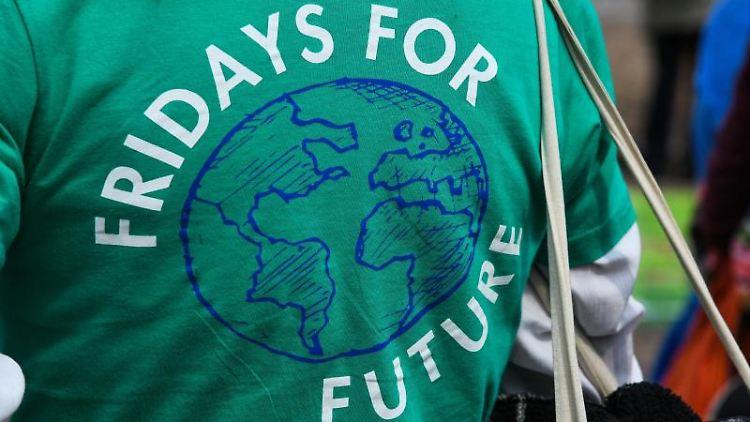 Eine Frau demonstriert in einem grünen T-Shirt mit der Aufschrift