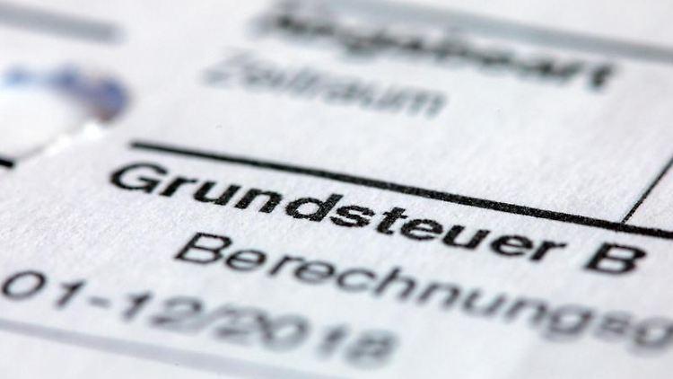 Ein Abgabenbescheid für die Entrichtung der Grundsteuer liegt auf einem Schreibtisch. Foto:Jens Büttner/Archivbild