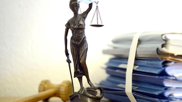 Eine modellhafte Nachbildung der Justitia steht neben Akten. Foto: Volker Hartmann/Archiv