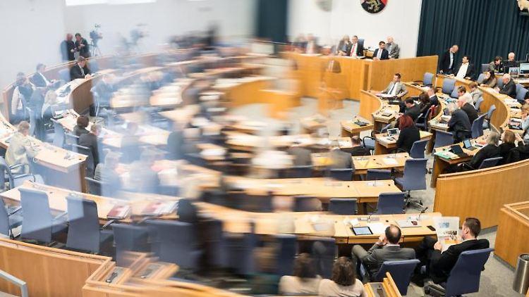 Abgeordnete sitzen im Landtag auf ihren Plätzen (teilweise durch eine Plexiglasscheibe unscharf zu sehen). Foto: Andreas Arnold/Archivbild