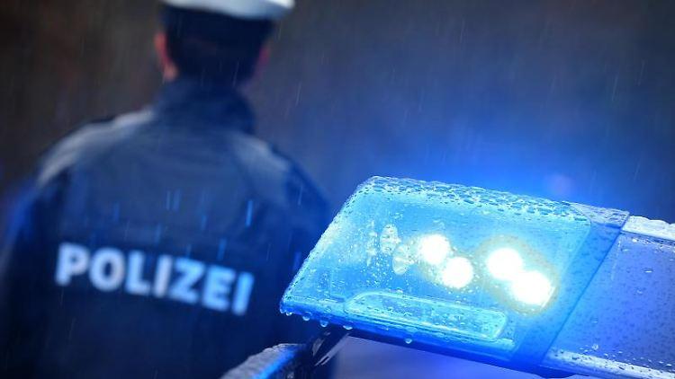 Ein Polizist steht im Regen vor einem Streifenwagen. Foto: Karl-Josef Hildenbrand/Archivbild