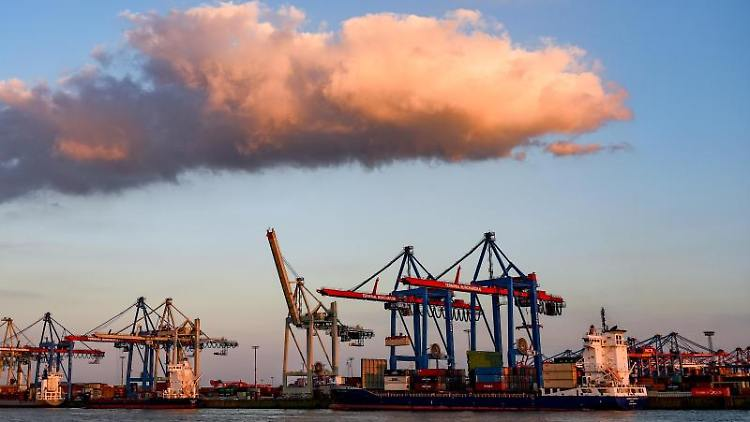 Containerschiffe werden im Hafen im Licht der untergehenden Sonne abgefertigt. Foto: Axel Heimken/Archiv