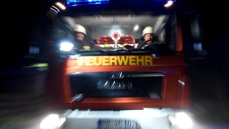 Männer der Feuerwehr sitzen in einem Löschfahrzeug. Foto: Carsten Rehder/Archivbild