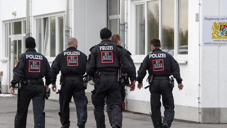 Polizisten gehen auf dem Gelände der Außenstelle Stephansposching des Ankerzentrums Deggendorf. Foto:Armin Weigel/Archiv