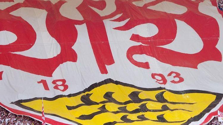 Stuttgarter Fans mit einem Banner mit dem Logo des VfB Stuttgart. Foto: Sebastian Kahnert/Archivbild