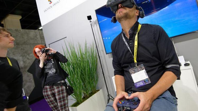 Ein Besucher spielt auf der Gamescom auf dem Stand des Landes Sachsen-Anhalt ein Computerspiel mit einer VR Brille. Foto: Henning Kaiser