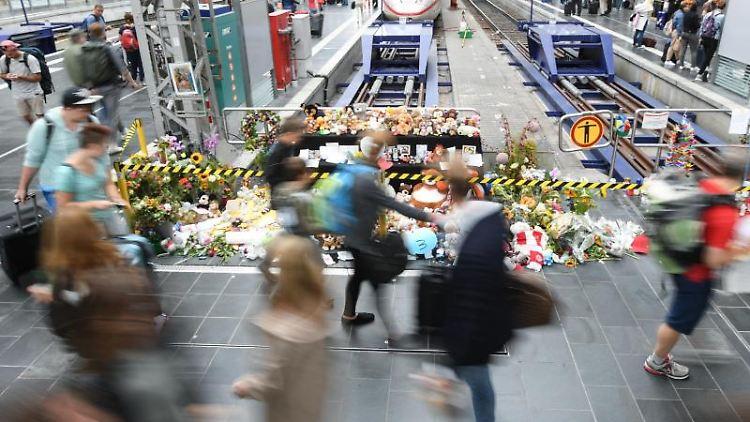 Passanten gehen am Gleis 7 des Hauptbahnhofs an einer Gedenkstelle vorbei. Foto: Arne Dedert/Archivbild