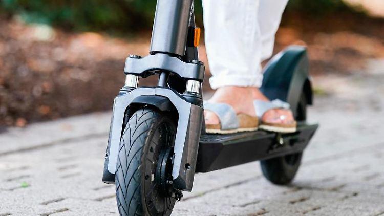 Eine Frau fährt einen E-Scooter. Foto: Uwe Anspach/Archivbild