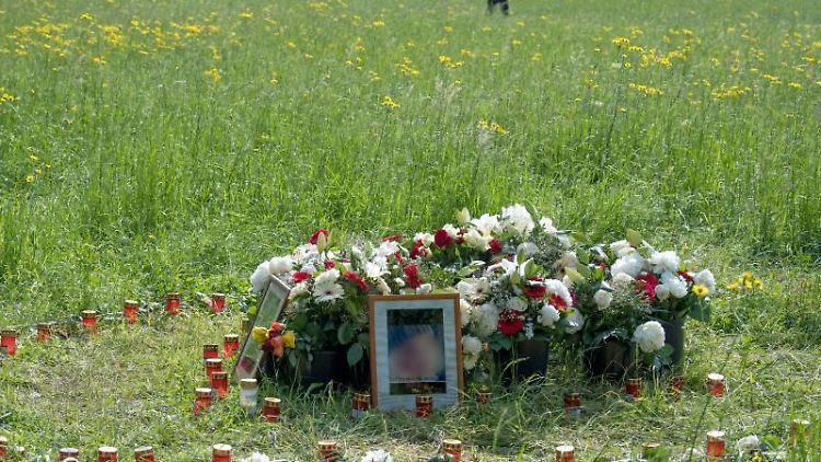 Blumen, Grablichter und Porträts der Getöteten stehen an der entsprechenden Stelle im Niddapark. Foto: Boris Roessler/Archivbild