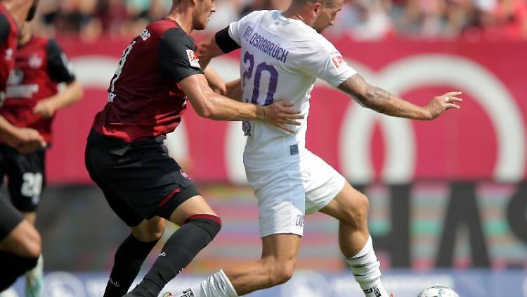 Der Nürnberger Asger Sörensen (l) kämpft mit dem Osnabrücker Marc Heider um den Ball. Foto: Daniel Karmann