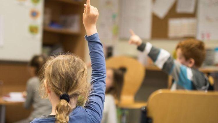 Schüler melden sich im Unterricht. Foto: Frank Rumpenhorst/Archivbild