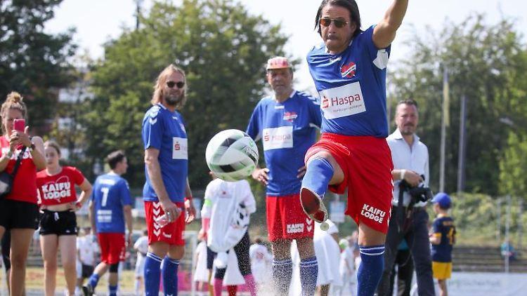 Jorge Gonzales, Choreograph und Model, schießt den Ball beim Aufwärmen zum Benefiz-Fußballspiel