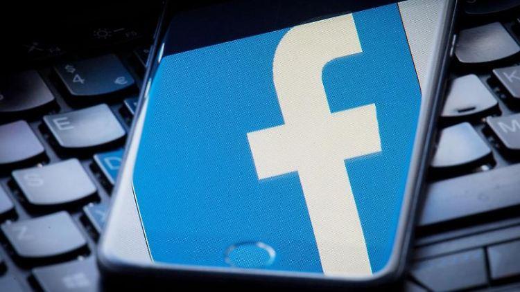 Das Facebook Logo wird auf einem Smartphone gespiegelt das auf einer Tastatur liegt