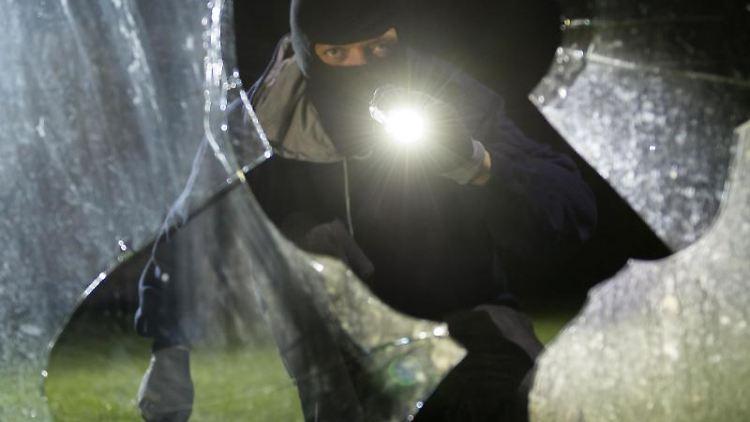 Ein fiktiver Einbrecher blickt in ein Haus. Foto: Daniel Maurer/Archiv