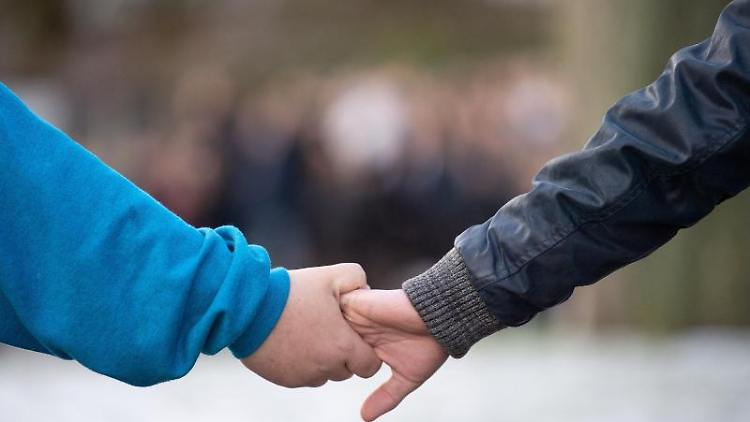 Menschen halten sich an der Hand. Foto:Sebastian Gollnow/Archivbild