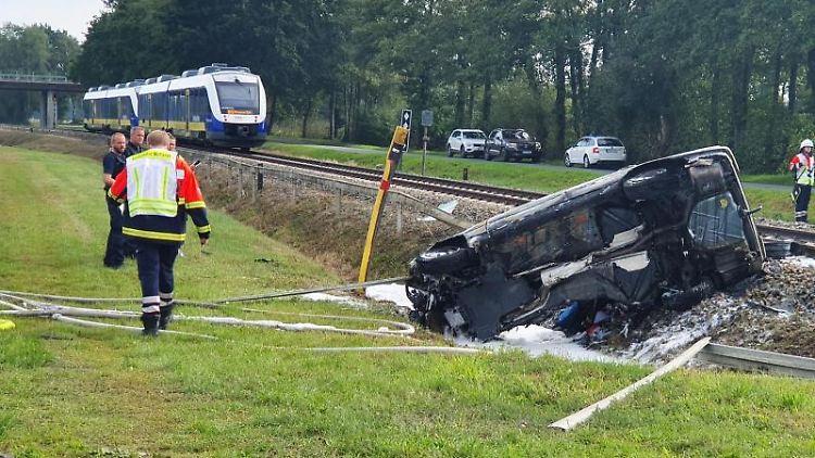 Rettungskräfte stehen an einer Unfallstelle nahe einem unbeschrankten Bahnübergang. Foto: Nord-West-Media TV