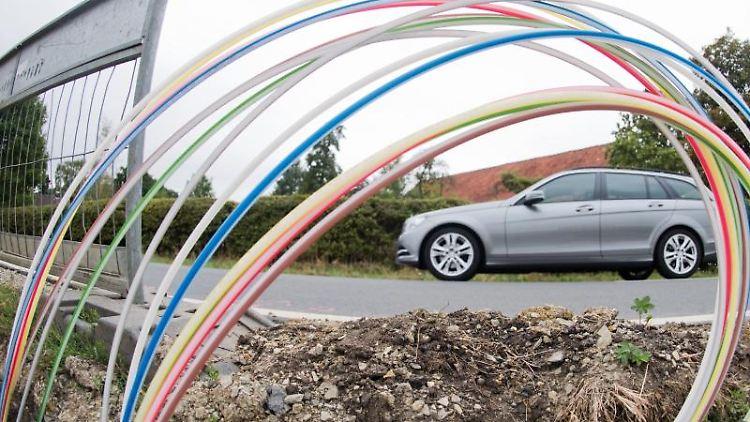 Ein Auto fährt an einer Baugrube mit Leerrohren für Glasfaserleitungen für schnelles Internet vorbei. Foto: Julian Stratenschulte/Archiv
