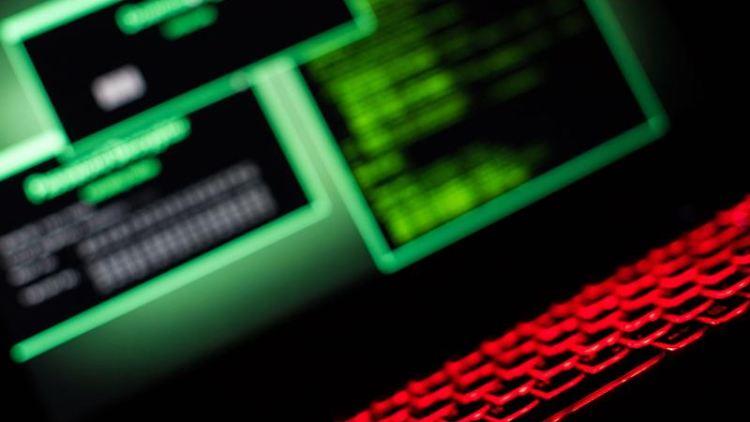 Eine Rot beleuchtete Tastatur steht vor einem Bildschirm auf dem fiktive Hackersoftware aufleuchtet. Foto: Lino Mirgeler/Archiv