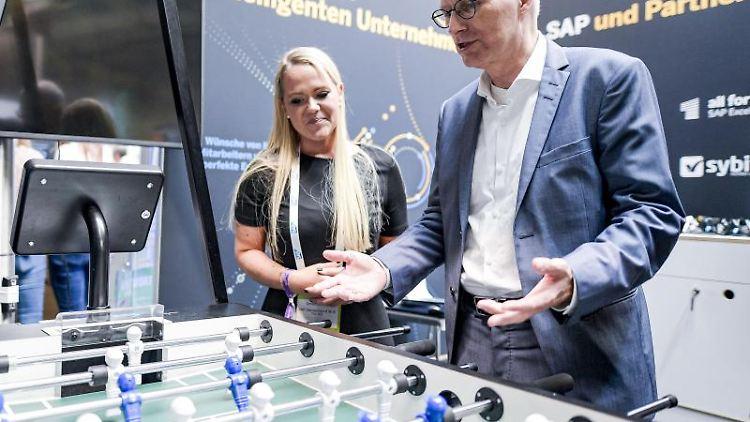 Peter Tschentscher (SPD) lässt sich beim Kongress solutions.hamburg einen digitalisierten Tischkicker erklären. Foto:AxelHeimken