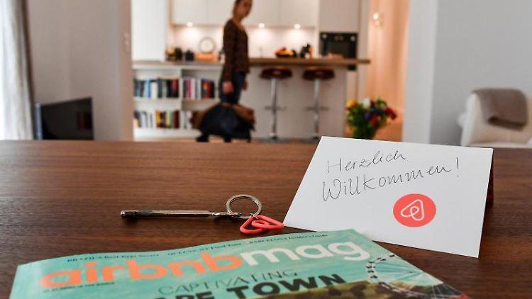 Ein Schlüssel, ein Airbnbmag-Magazin und eine Willkommenskarte liegen in der Wohnung eines Airbnb-Gastgebers. Foto: Jens Kalaene/Archivbild