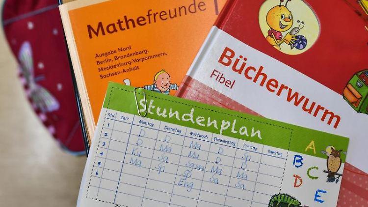 Bücher und ein Stundenplan liegen auf der Schulbank eines Schülers. Foto:Patrick Pleul/Archivbild